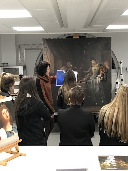 Colour photograph showing Christina Young, principal investigator on the PISTACHIO research project, standing in front of a painting and explaining the role of UV imaging in investigating artworks during to a group of S3 students during a visit to the museum from Drumchapel High School students (copyright The Hunterian/University of Glasgow)